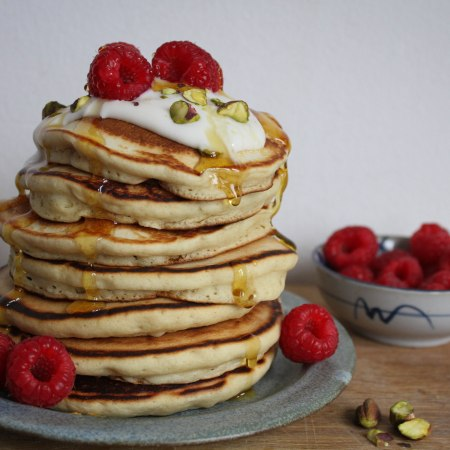 Vegan pancake stack with raspberries and syrup